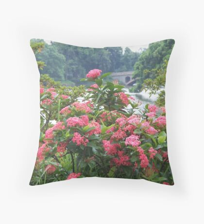 Beautiful red flowers in front of lake surrounded by trees in Asia Throw Pillow