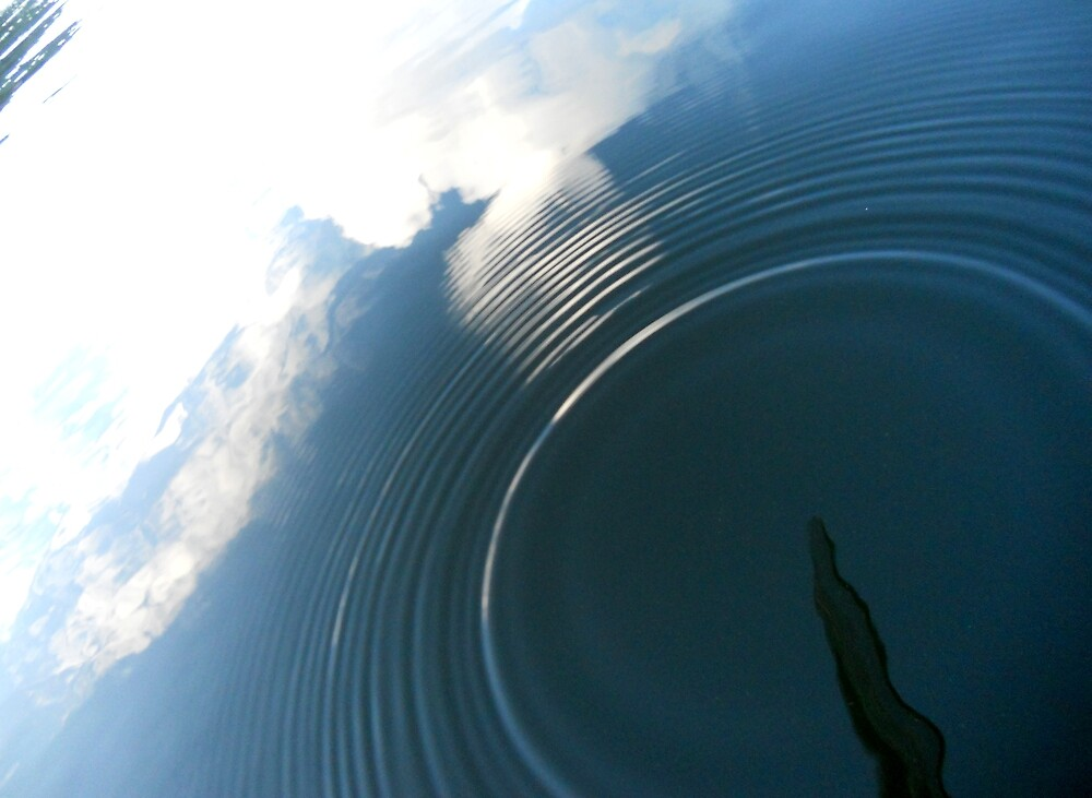 Reflected sky in a glassy lake surface  by Hugh Mitchell
