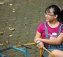 little girl sit down in park by bayu harsa