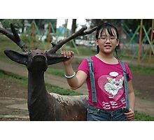 little girl stand up beside deer statue Photographic Print
