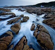 Rockpools drain after a large wave at sunset by Michael Gay