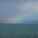Rainbow out to sea by Janette Anderson