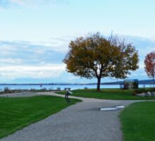 Beautiful crescent beach in late summer in White Rock, BC. Landscape picture of green grasses, blue sky, early fall yellow leaves tree and sea.  Sticker