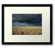 Stubble field under ominous sky Framed Print
