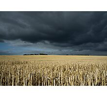 Stubble field under ominous sky Photographic Print