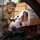 Bride watches female chauffeur checking engine of broken down car. by imageunlimited