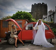 Bride tries to hitch a lift as female chauffeur sits on wheel arch of broken down car. by imageunlimited