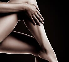 Closeup of Bare Woman Legs on Black Background art photo print by ArtNudePhotos