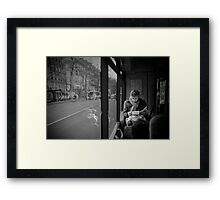 Reading in the bus Framed Print