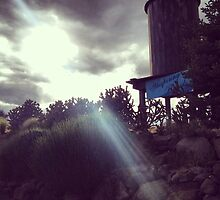 Water Tower with Sun Breaking Though Gray Skies by JULIENICOLEWEBB
