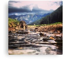 Creek Flowing Over River Rocks Beneath The Mountains Canvas Print