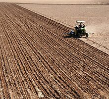 tractor ploughing field by nialloc