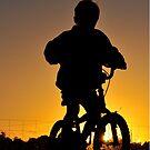 boy on bike in sunrise by Coralie Plozza