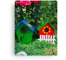 Two small birdhouses in a garden Canvas Print