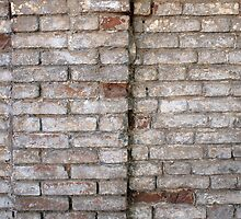 Detail of a wall of an old red brick with white coating by vladromensky