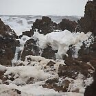 Foam spilling over rocks. by Eunice Atkins