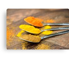 Warm Orange and Yellow Indian Cooking Spices on Silver Spoons Canvas Print