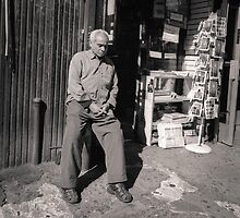 New York City: Man alone at store front by Ron Greer