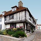 Tudor House with flower bed and cobbled street by Richard Majlinder