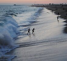 California beach running from waves in sunset by bethischeery