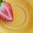 1/2 strawberry in a yellow plate by Sandra Guzman