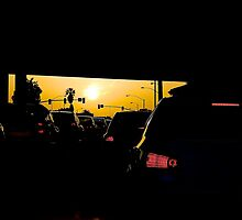 Yellow-orange sunset as seen from under a bridge in los angeles traffic by kyleO