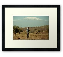 [man checking his phone at the foot of Mount Kilimanjaro] Framed Print