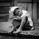 A young Hindu boy lost in his thoughts by Matt Bottos