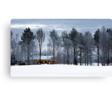 Yellow house in winter time Canvas Print