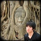 Young man and buddah  at Wat Mahathat, Thailand by Catherine Ames