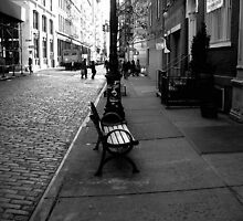 a bench on a cobblestone street by ShellyKay