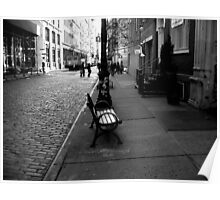 a bench on a cobblestone street Poster