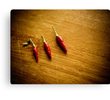 Three red chilies all in a row Canvas Print