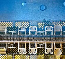 Chairs in pool reflection  by richard  webb