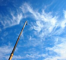 The boom of the crane on a diagonal against a blue sky by vladromensky