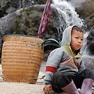 Kid sitting on a rock by Tom Shapland