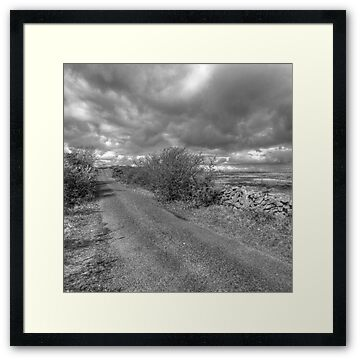 Black and white photo of scenic country road in The Burren in county Clare near Mullaghmore mountain in The Burren National Park