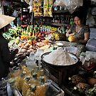 Woman at food stall preparing fresh pineapple. Vung Tau, Vietnam by Sheldon Levis