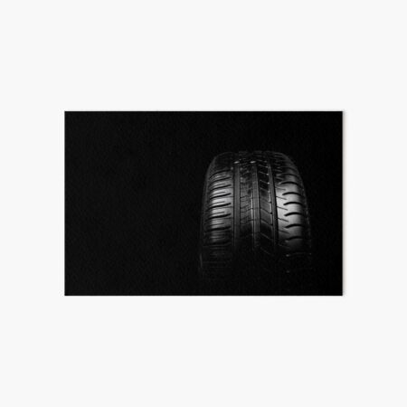 Car tyre isolated on a black background Art Board Print