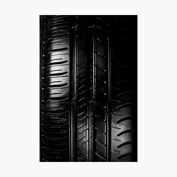 Close up view of car tyre isolated on a black background Photographic Print