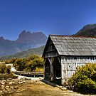 A boathouse nestles in front of the cradle mountain by Madhusudan