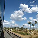 Railway track and puffy white clouds by Shiju Sugunan