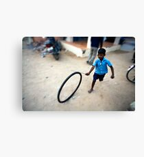 Boy playing with tyre Canvas Print