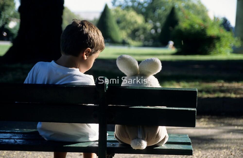 Boy (7-9) sitting on park bench with teddy bear by Sami Sarkis