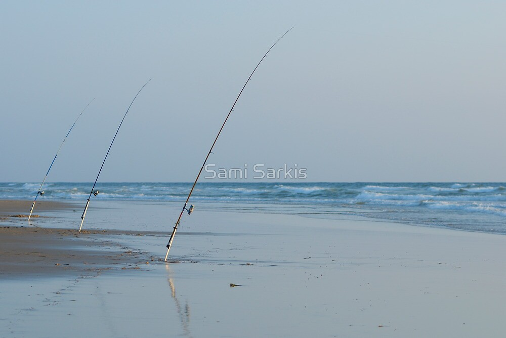Three fishing rods on beach by Sami Sarkis