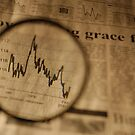 View of graph in newspaper trough magnifying glass by Sami Sarkis