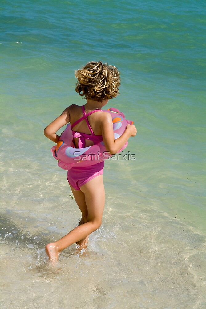 Girl running into water on beach by Sami Sarkis