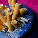 Cigarette butts in ashtray by Sami Sarkis
