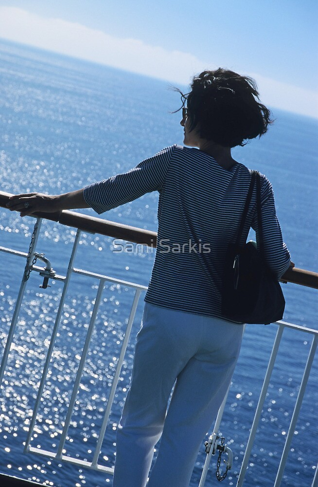 Woman looking out to sea from deck of boat by Sami Sarkis