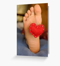 Valentine heart hanging on girl's barefeet Greeting Card